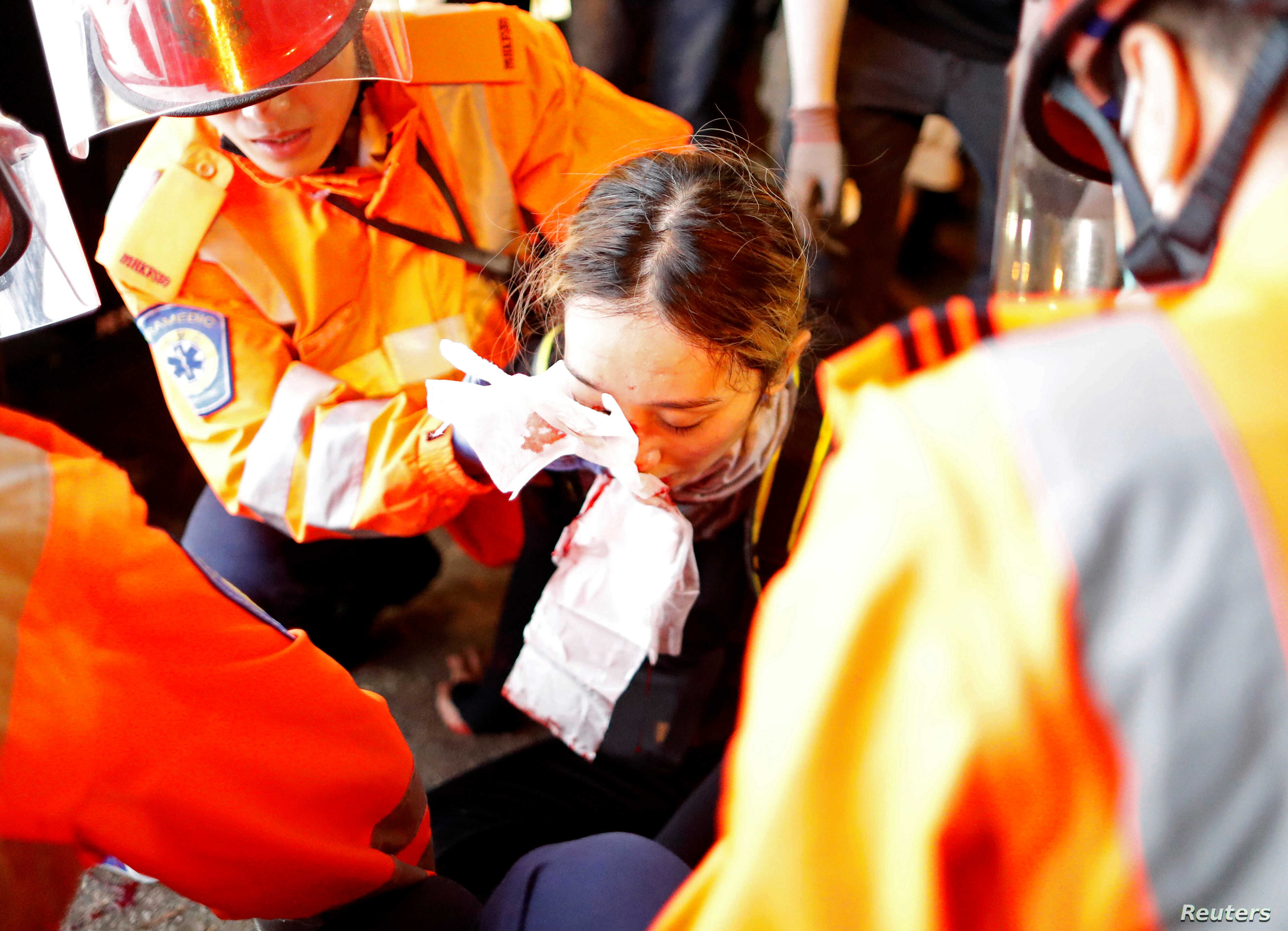 An injured young female medic receives medical assistance after being hit by a pellet round in the right eye during a demonstration in Tsim Sha Tsui neighbourhood in Hong Kong, Aug. 11, 2019.