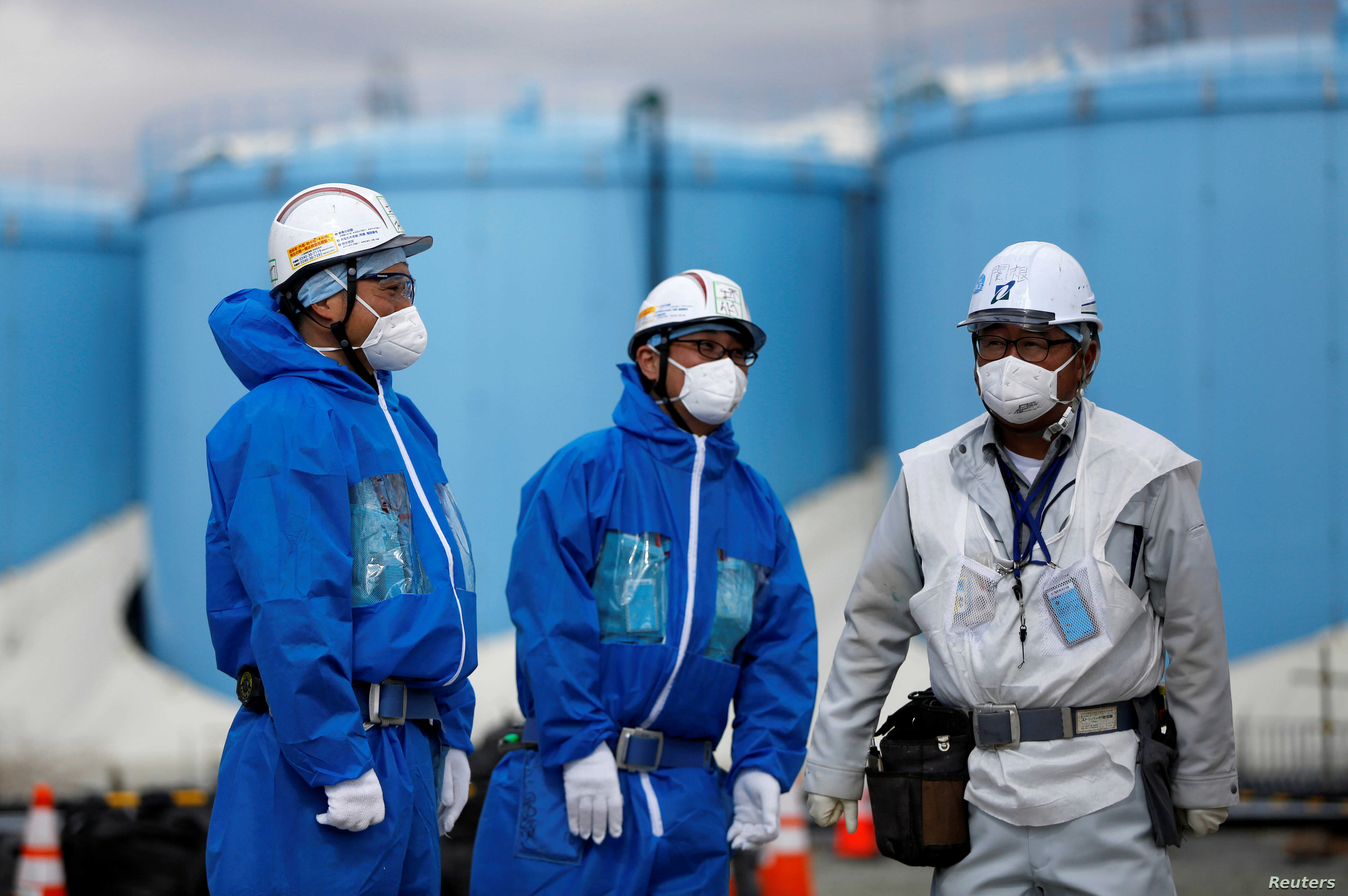 FILE- Workers are seen in front of storage tanks for radioactive water at Tokyo Electric Power Co's tsunami-crippled Fukushima Daiichi nuclear power plant in Okuma town Fukushima prefecture Japan Feb. 18 2019