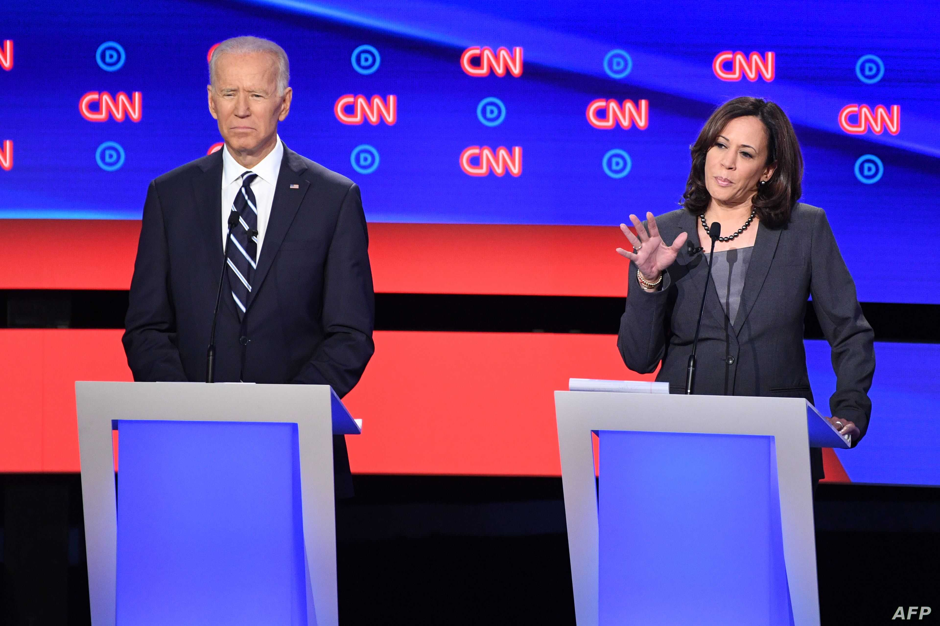 Democratic presidential hopeful U.S. Senator from California Kamala Harris, right, delivers her closing statement flanked by former Vice President Joe Biden during the Democratic primary debate hosted by CNN at the Fox Theatre in Detroit, July 31, 2019.
