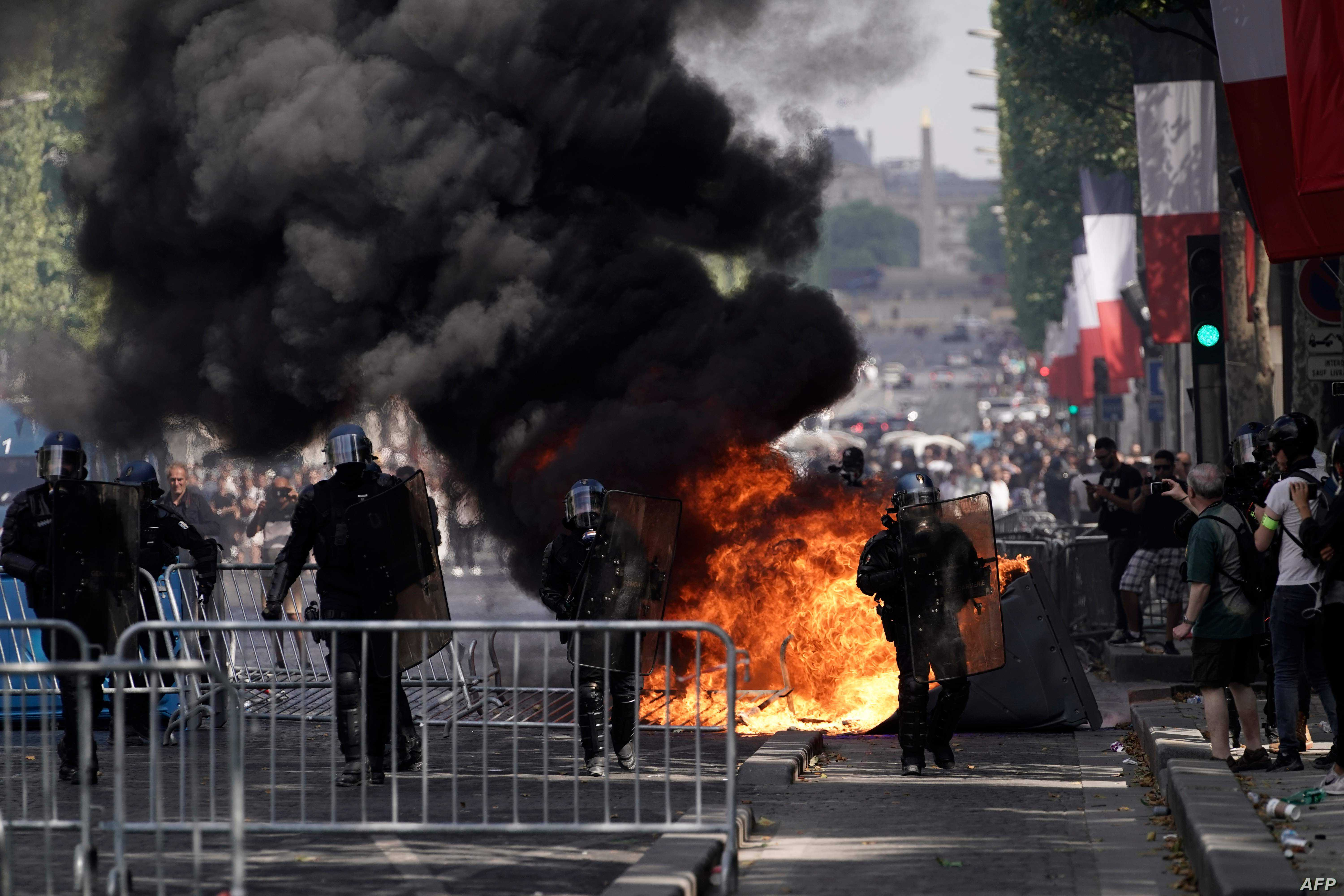 Members of the Gendarmerie stand in front of fences and a fire as protesters linked to the Yellow Vests movement (unseen) take part in a demonstration on the side of the annual Bastille Day ceremony, July 14, 2019, on the Champs-Elysees in Paris.