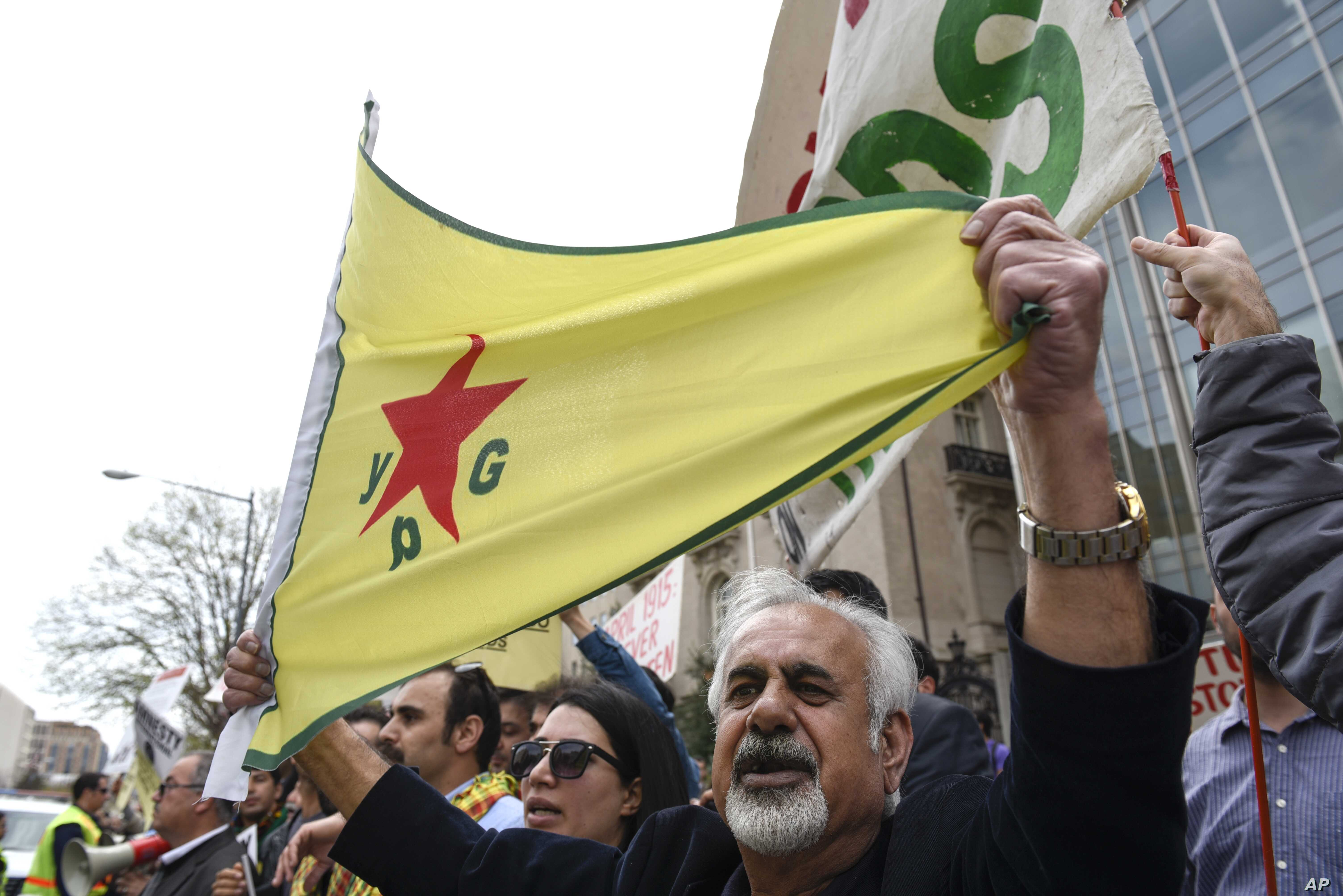 A man holds a flag of YPG, a Syria-based Kurdish militant group, during a protest against Turkish President Recep Tayyip Erdogan in front of Brookings Institution in Washington, Thursday, March 31, 2016, where President Erdogan was speaking. (AP…
