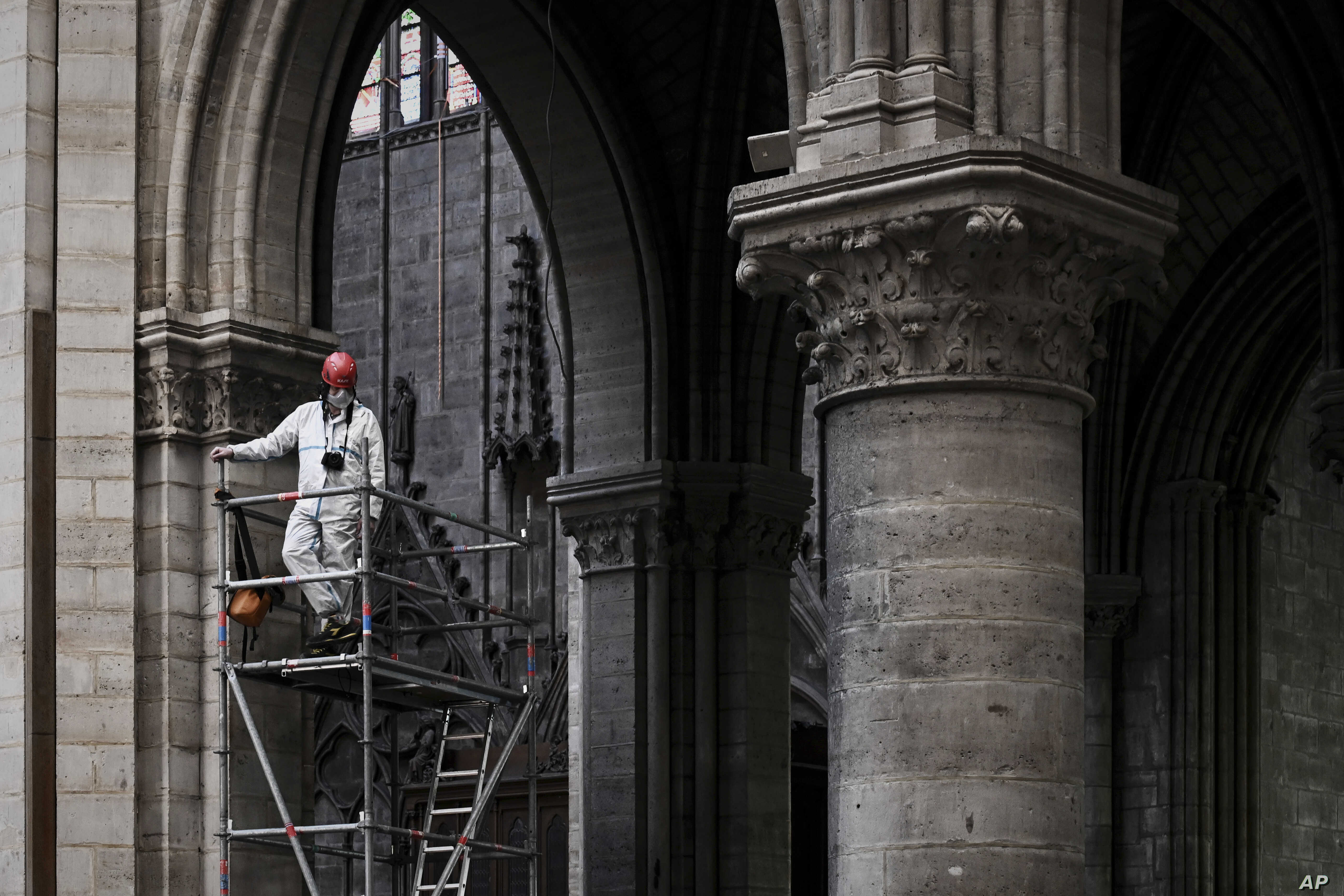 A worker stands on scaffolding during preliminary work inside the Notre Dame de Paris Cathedral, Wednesday May 15, 2019 in Paris.