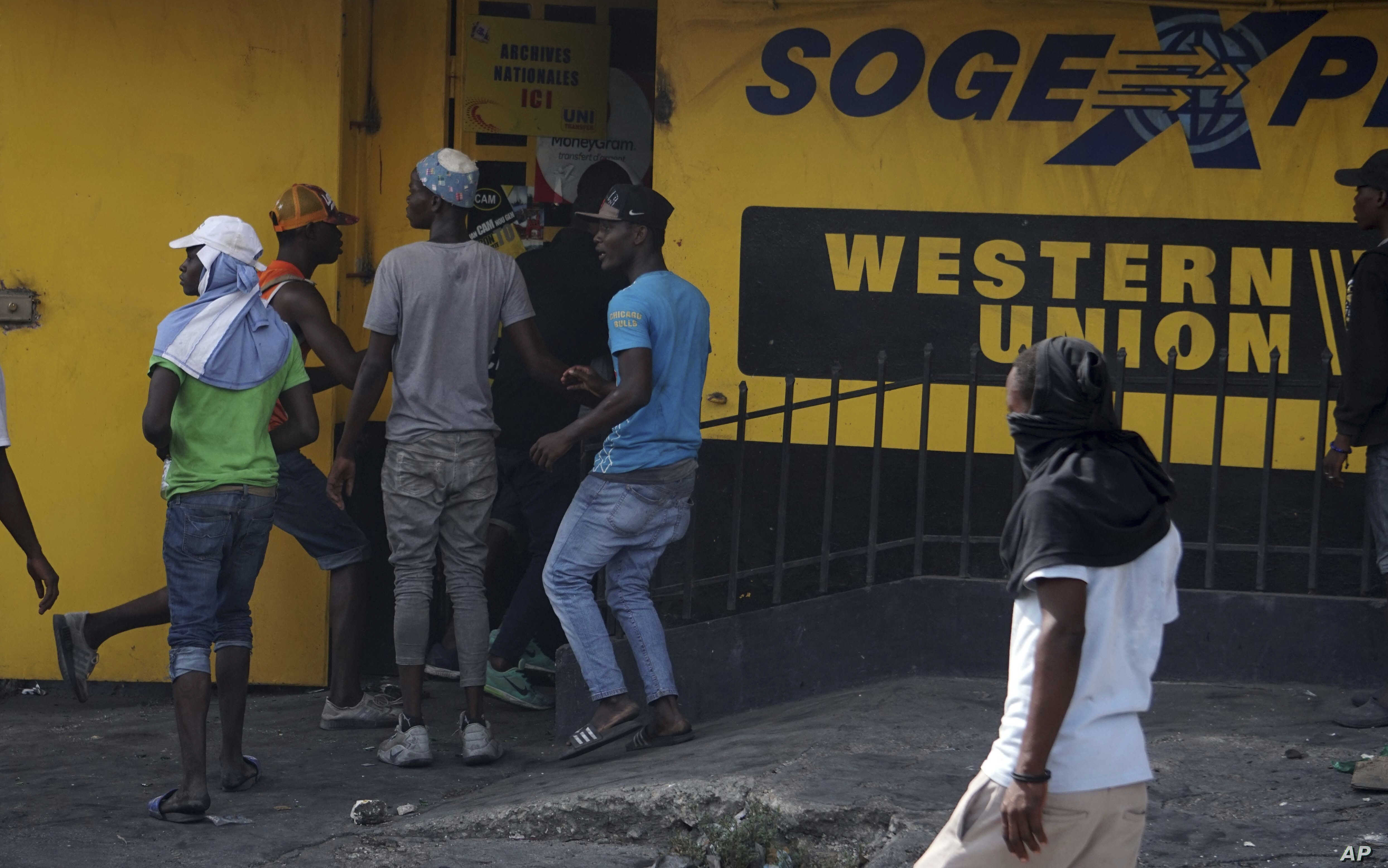 Protesters loot a money transfer office during a protest demanding the resignation of President Jovenel Moise in Port-au-Prince, Haiti, Thursday, June 13, 2019.