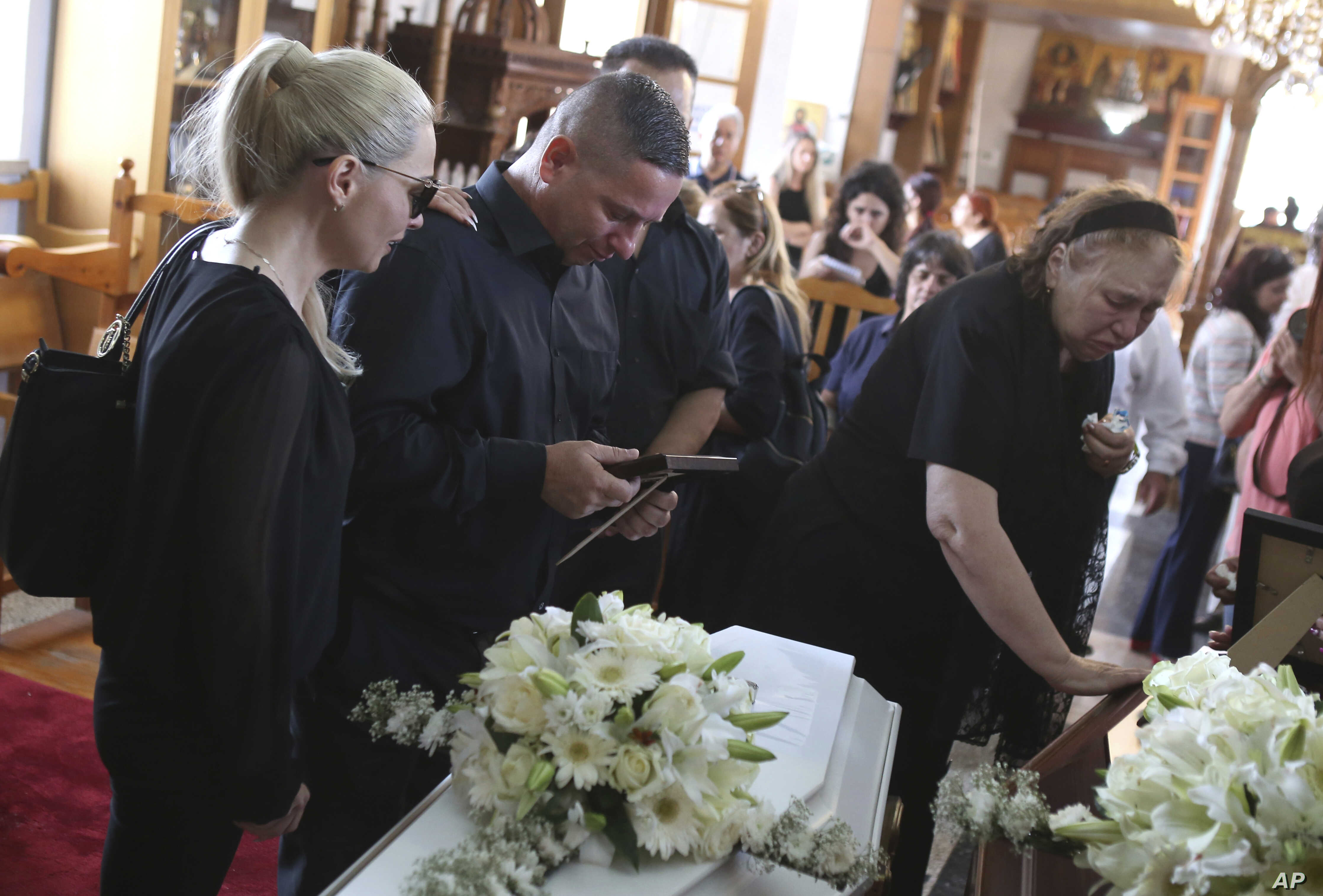 Relatives mourn in Arediou, Cyprus,  June 13, 2019, for two suspected victims of a serial killer.