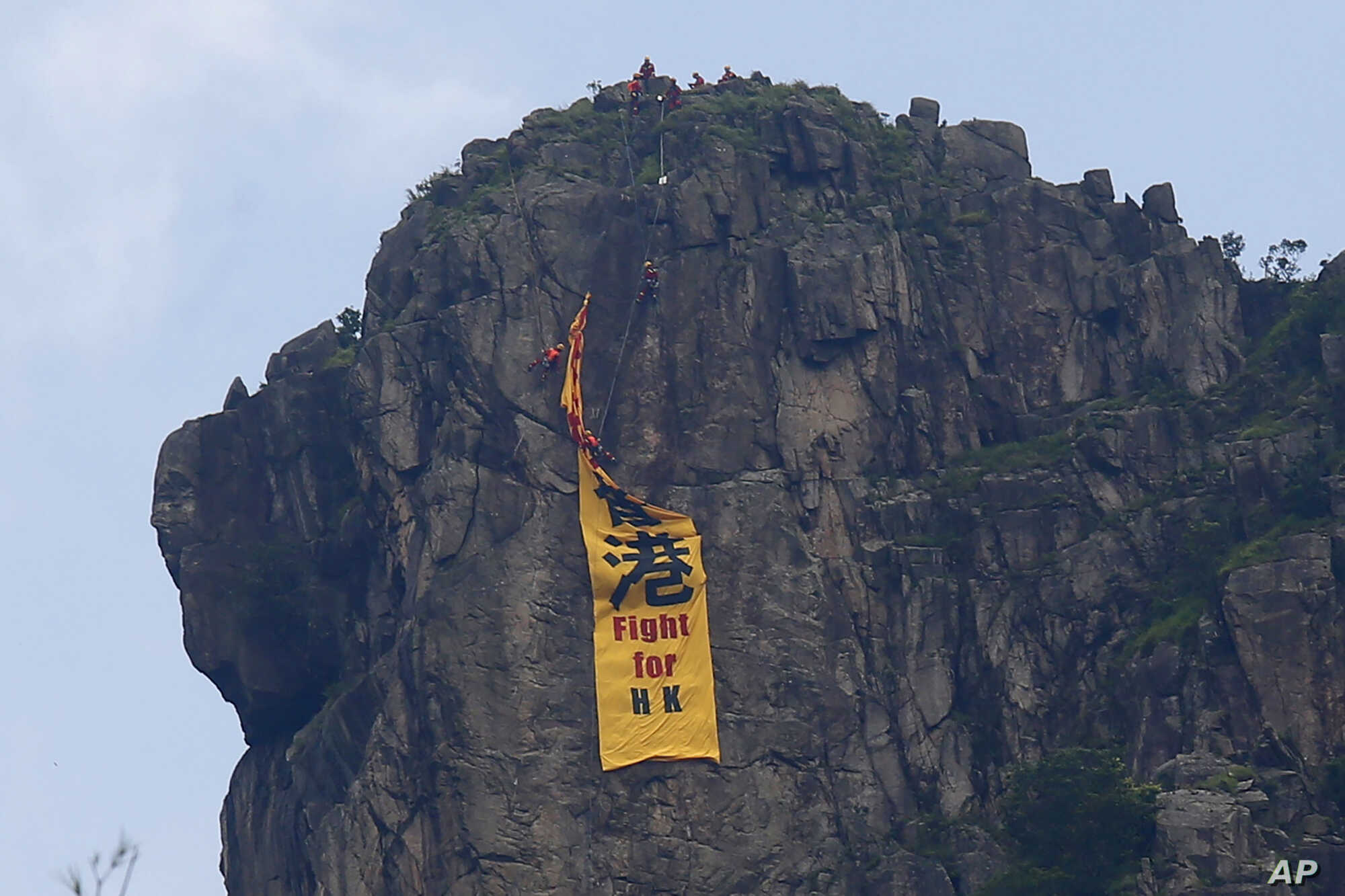 "Firefighters remove a yellow banner with the words ""Fight for Hong Kong"" in Chinese and English which is hung on the Lion Rock mountain by pro-democracy protesters in Hong Kong, Sunday, June 16, 2019. Hong Kong was bracing Sunday for another massive protest over an unpopular extradition bill that has highlighted the territory's apprehension about relations with mainland China, a week after the crisis brought as many as 1 million into the streets. (AP Photo/Kin Cheung)"