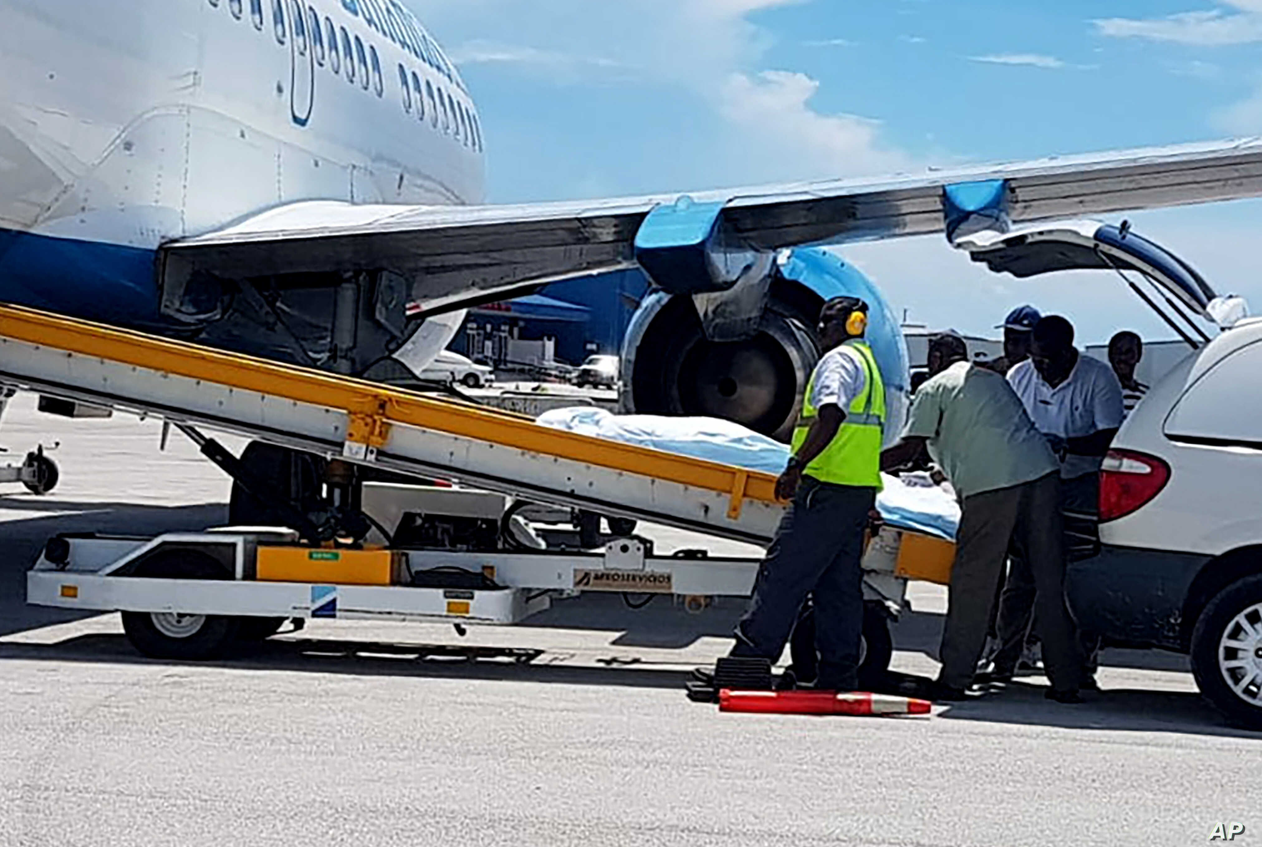 In this handout photo released by the Bahamas ZNS Network, employees oversee the arrival of the bodies of four women and three men, including billionaire coal entrepreneur Chris Cline and his daughter, at the airport in Nassau, Bahamas, Friday, July…