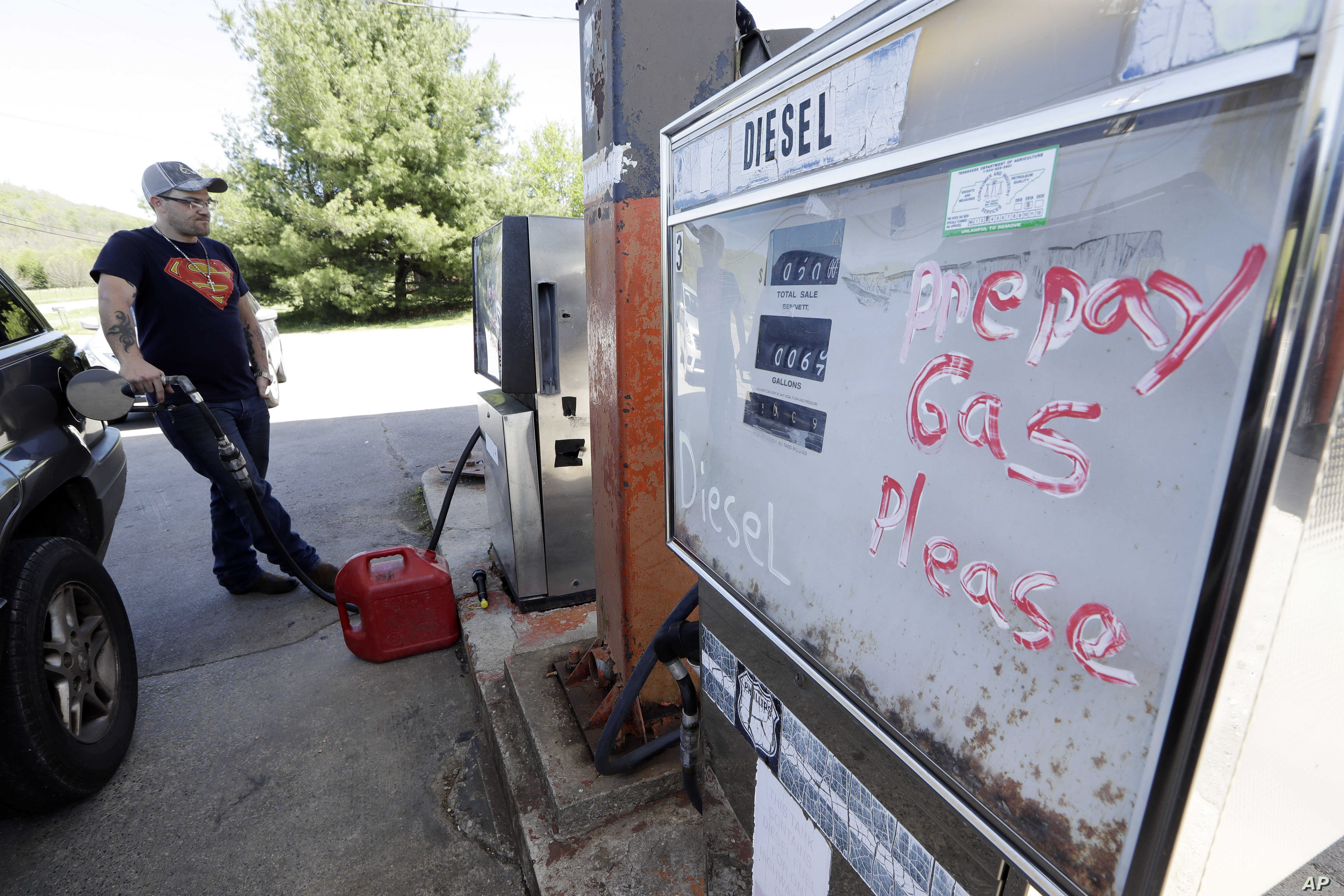 In this April 16, 2019, photo, Johnny Gibbs fills up a car with gas after finding someone to give him a ride to do errands in Liberty, Tenn. Gibbs has been trying to get a valid driver's license for 20 years, but he can't afford it. To punish him…