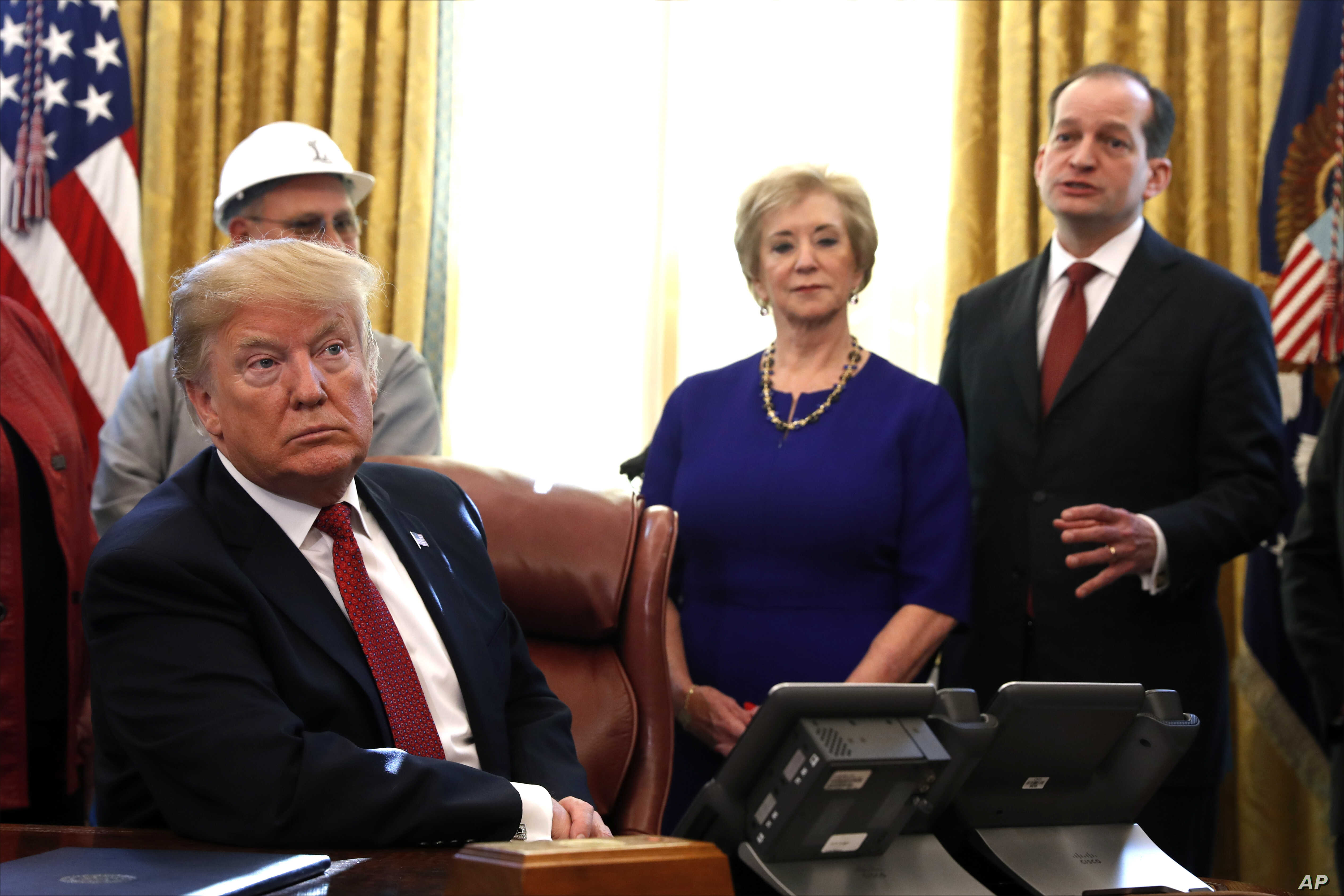 President Donald Trump listens as Labor Secretary Alex Acosta, right, speaks during a meeting with American manufacturers in the Oval Office of the White House, Thursday, Jan. 31, 2019, in Washington. Trump was signing an executive order pushing…