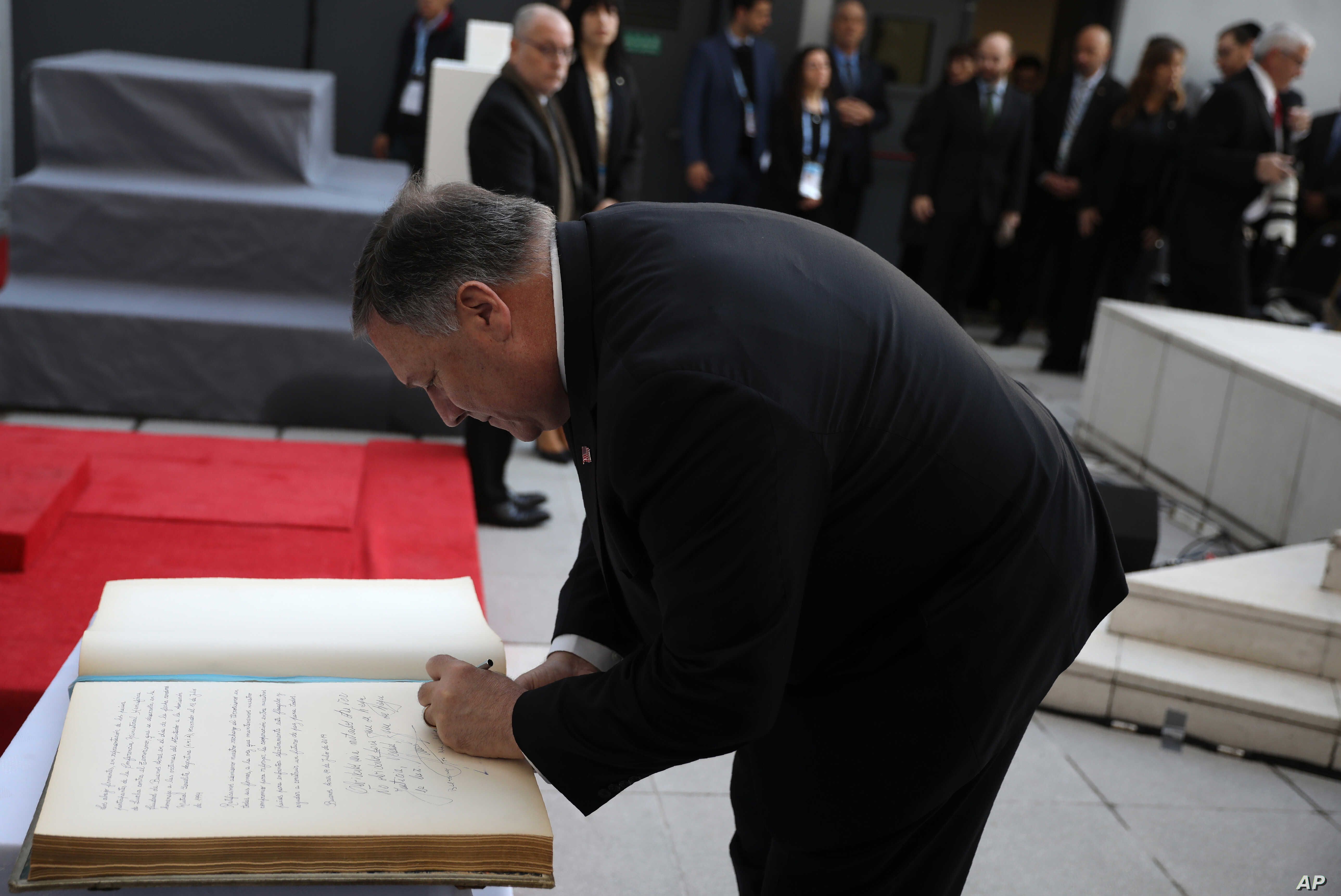 U.S. Secretary of State Mike Pompeo signs a guest book during a memorial service marking the death of 85 people who died in a 1994 bombing blamed on Hezbollah, in Buenos Aires, Argentina, Friday, July 19, 2019.  Argentine prosecutors blame Iranian…