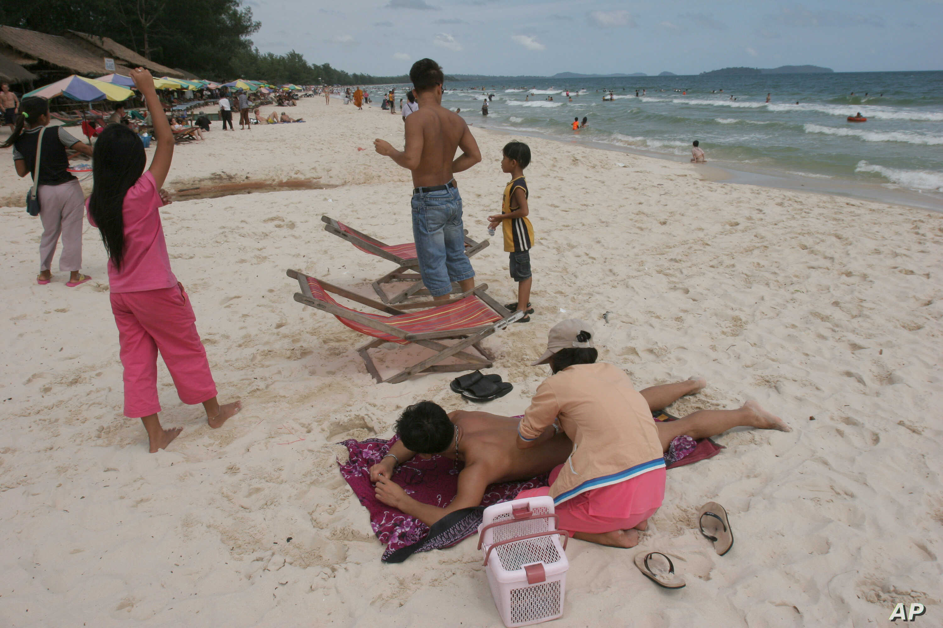 A Cambodian woman gives massage to a tourist on the beach of Sihanoukville, some 185 kilometers (115 miles)  southwest of Phnom Penh, Cambodia July 29, 2006. Cambodia's government has given its permission for six local and foreign companies to…