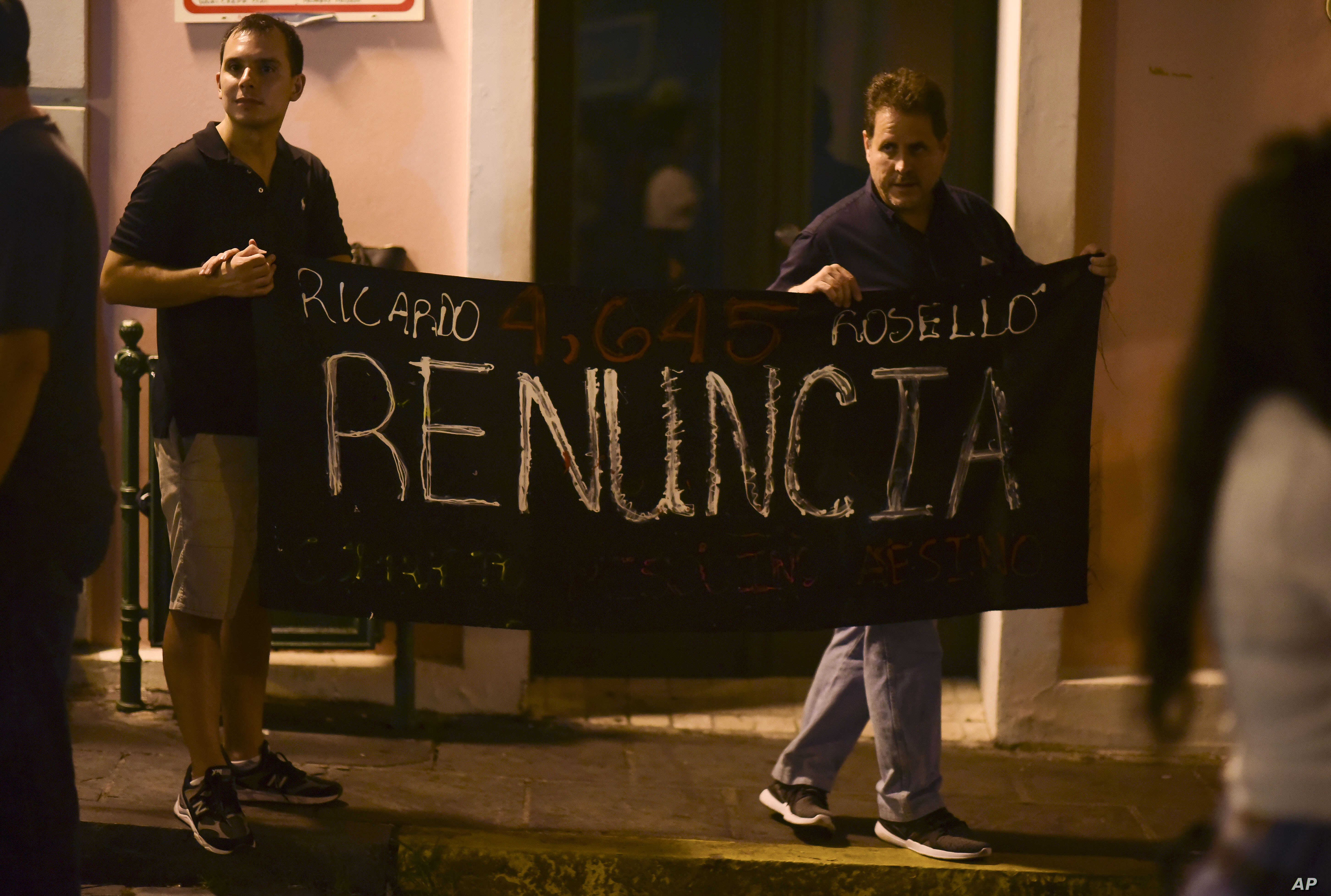 """Citizens carry a banner that reads """"Ricardo Rosello, renounce"""" during a protest denouncing a wave of arrests for corruption that has shaken the country and demanding Gov. Ricardo Rosello resign, in San Juan, Puerto Rico, July 11, 2019."""