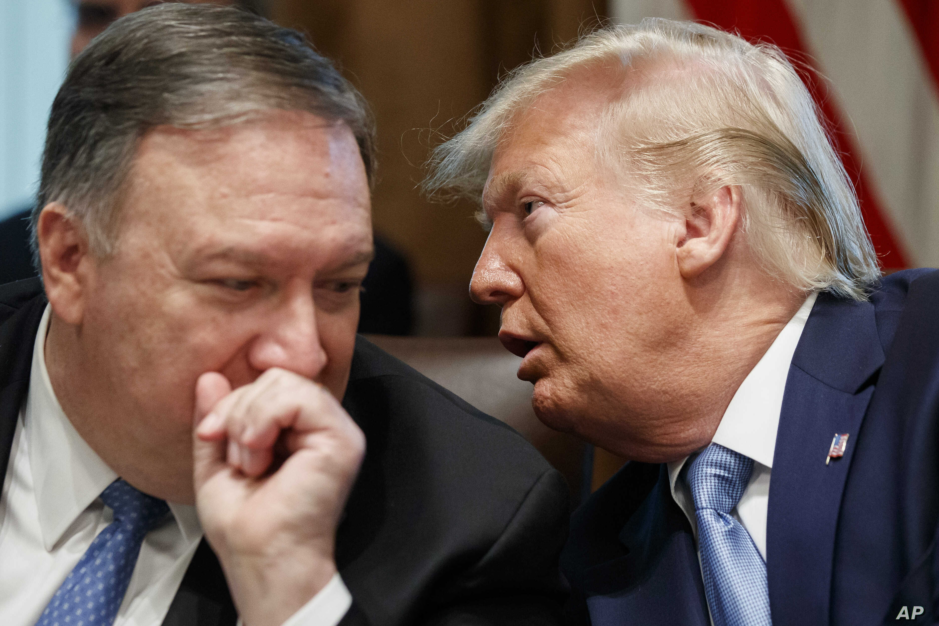 Secretary of State Mike Pompeo, left, and President Donald Trump whisper during a Cabinet meeting in the Cabinet Room of the White House, Tuesday, July 16, 2019, in Washington. (AP Photo/Alex Brandon)