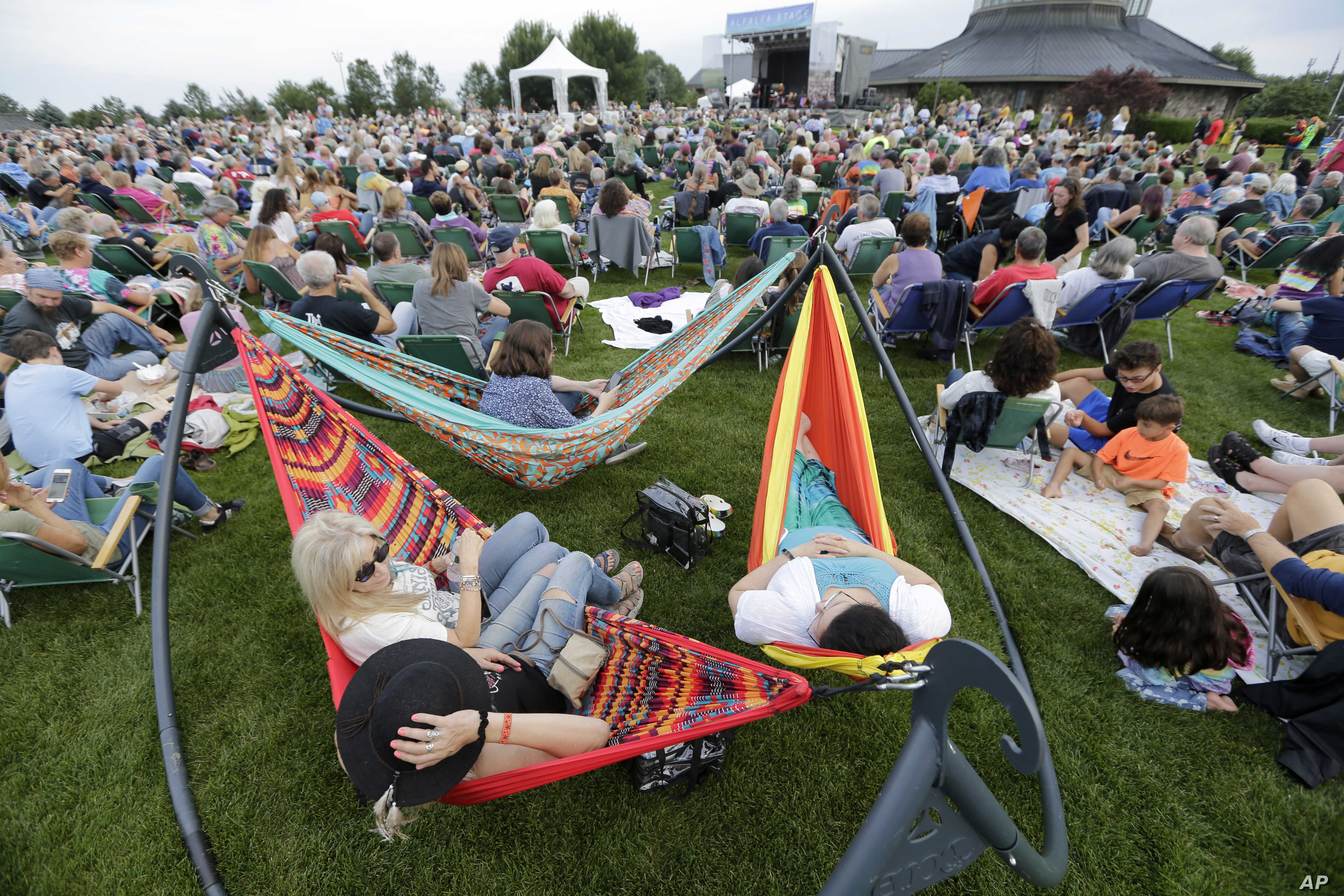 People enjoy a concert by Arlo Guthrie at a Woodstock 50th anniversary event in Bethel, N.Y., Aug. 15, 2019.People enjoy a concert by Arlo Guthrie at a Woodstock 50th anniversary event in Bethel, N.Y., Aug. 15, 2019.