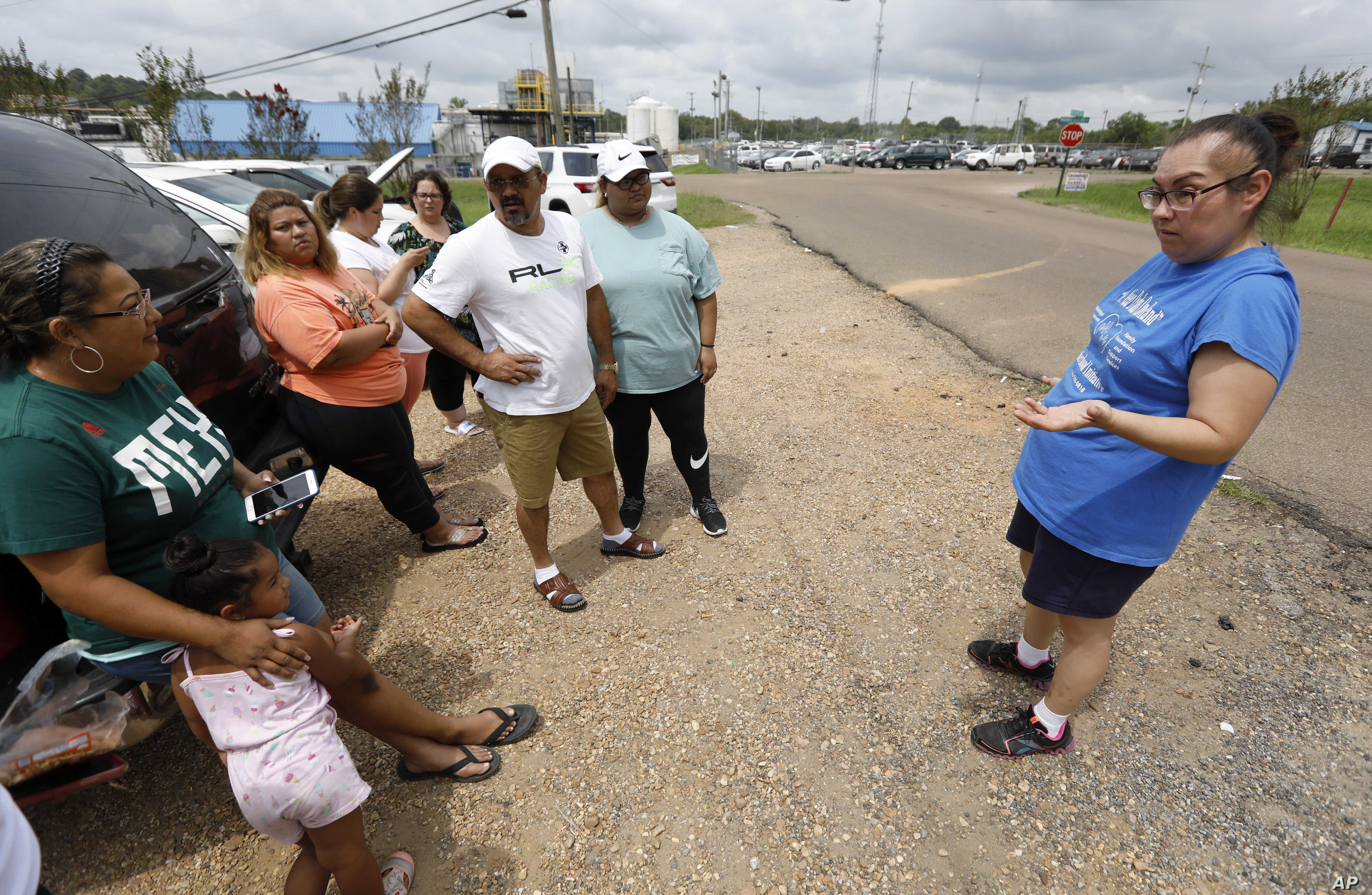 Gabriela Rosales, right, confers with friends outside the employee entrance to the Koch Foods Inc., plant in Morton, Miss., Aug. 8, 2019, that was raided Wednesday by U.S. immigration officials.
