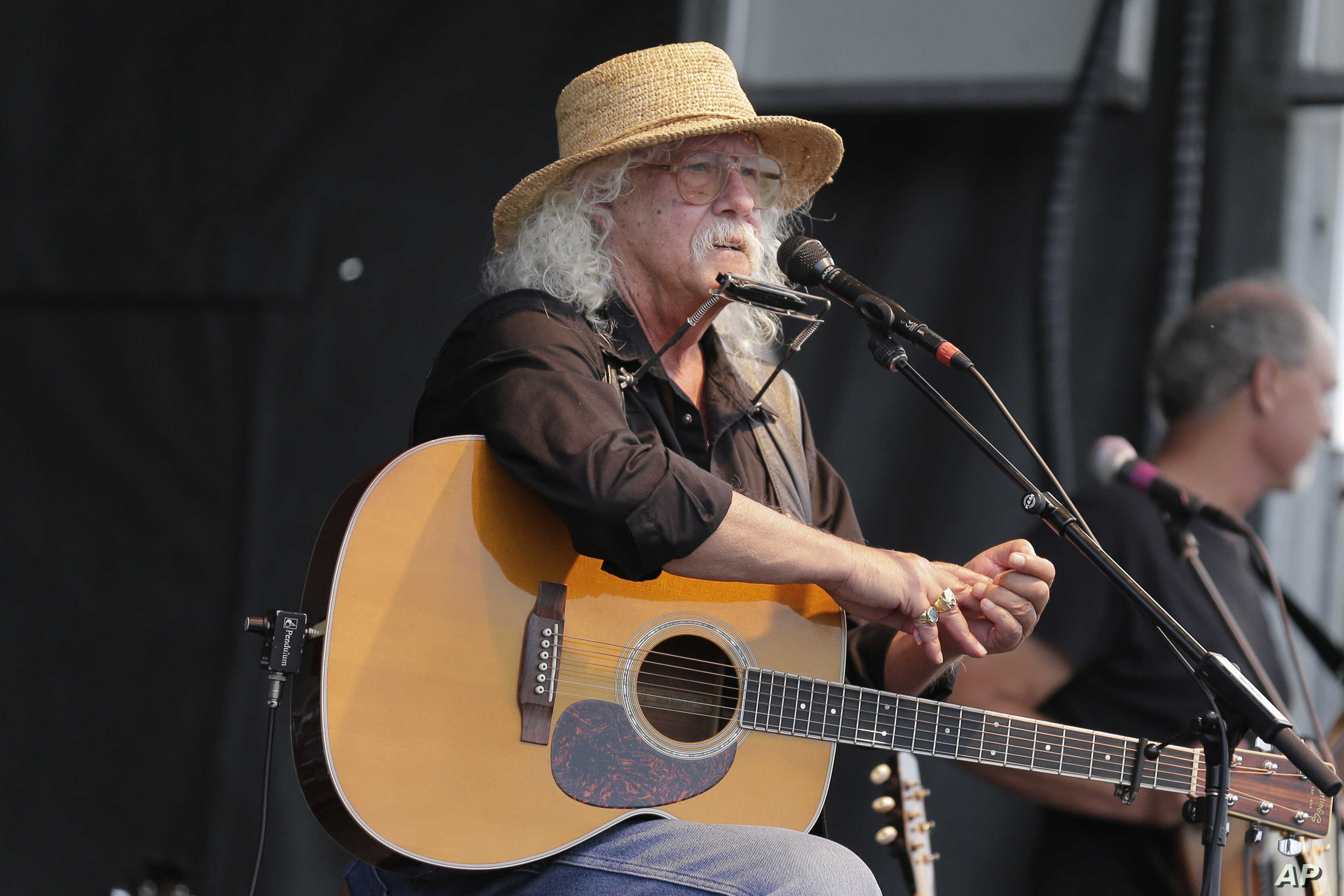 Arlo Guthrie talks during a concert at a Woodstock 50th anniversary event in Bethel, N.Y., Aug. 15, 2019. Bethel Woods Center for the Arts is hosting a series of events Thursday through Sunday at the bucolic 1969 concert site.