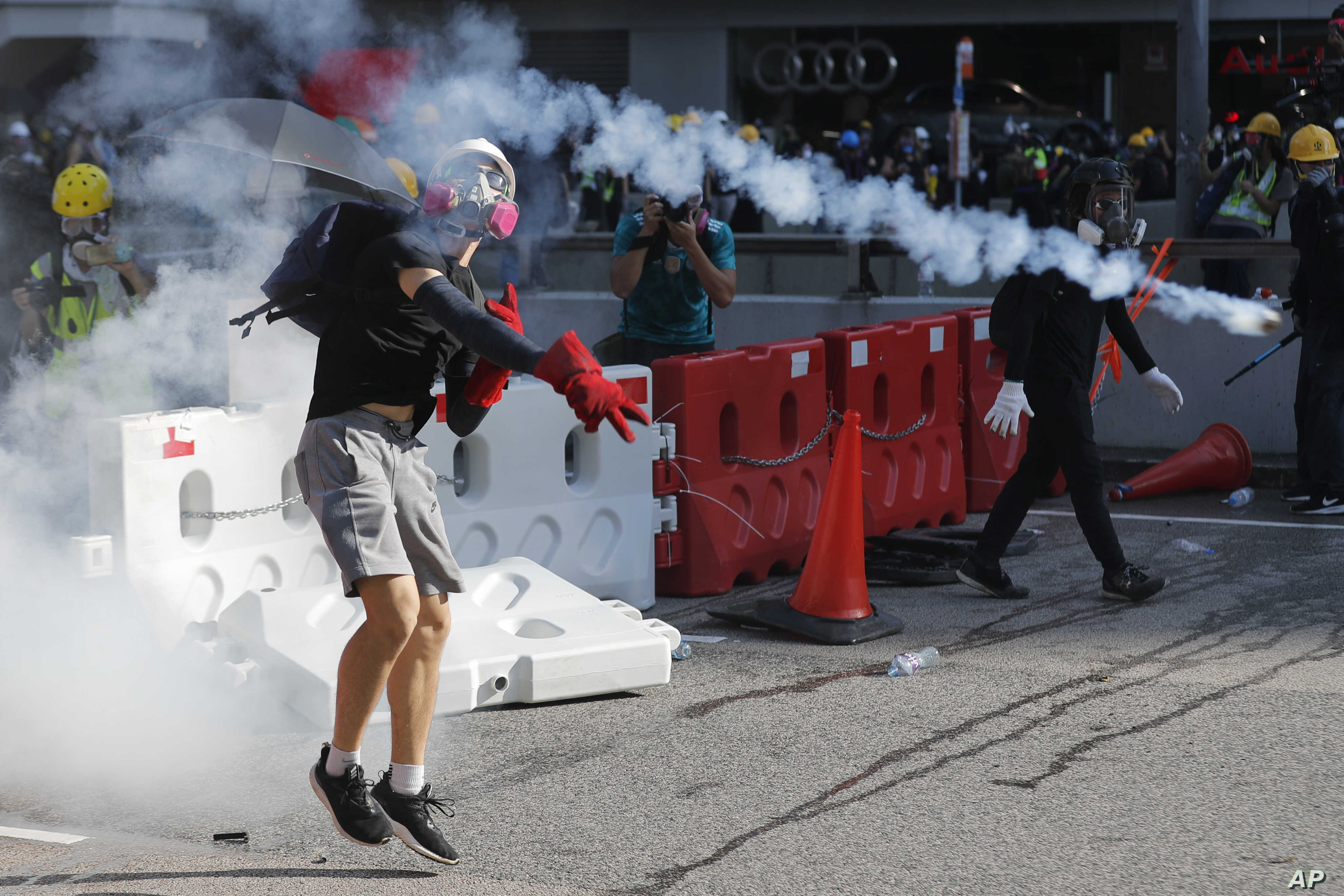FILE - A protester throws back a tear gas canister during demonstrations in Hong Kong, Aug. 5, 2019.