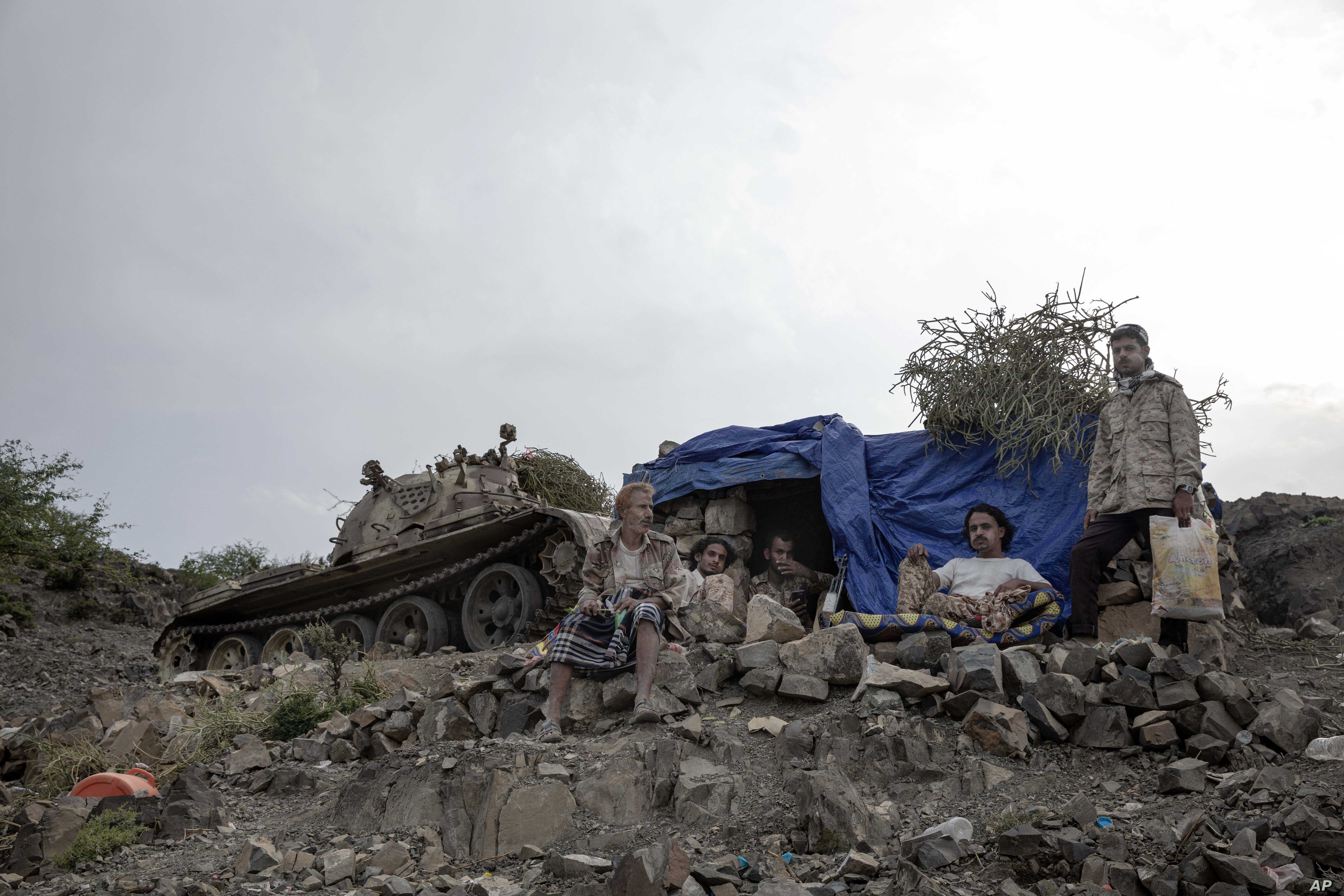 Fighters from a militia known as the Security Belt, that is funded and armed by the United Arab Emirates, take a break, Aug. 5, 2019, to chew Qat, a fresh leaf chewed for its stimulating effects, at the Gabhet Hajr frontline with Houthi rebels, in Yemen's Dhale province.