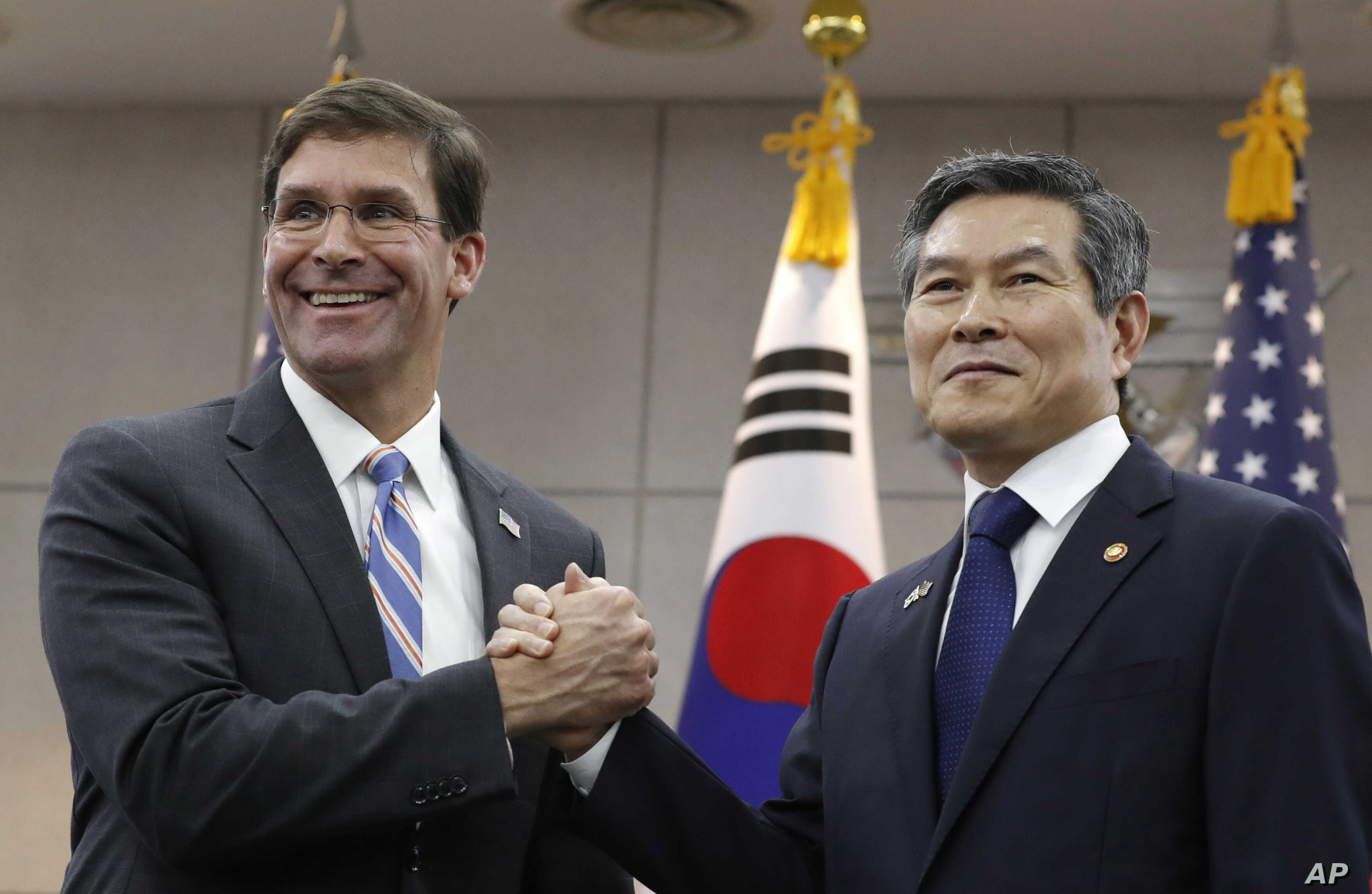 U.S. Defense Secretary Mark Esper, left, and South Korean Defense Minister Jeong Kyeong-doo, right, hold their hands ahead of a meeting at Defense Ministry in Seoul, South Korea, Friday, Aug. 9, 2019. (AP Photo/Lee Jin-man, Pool)