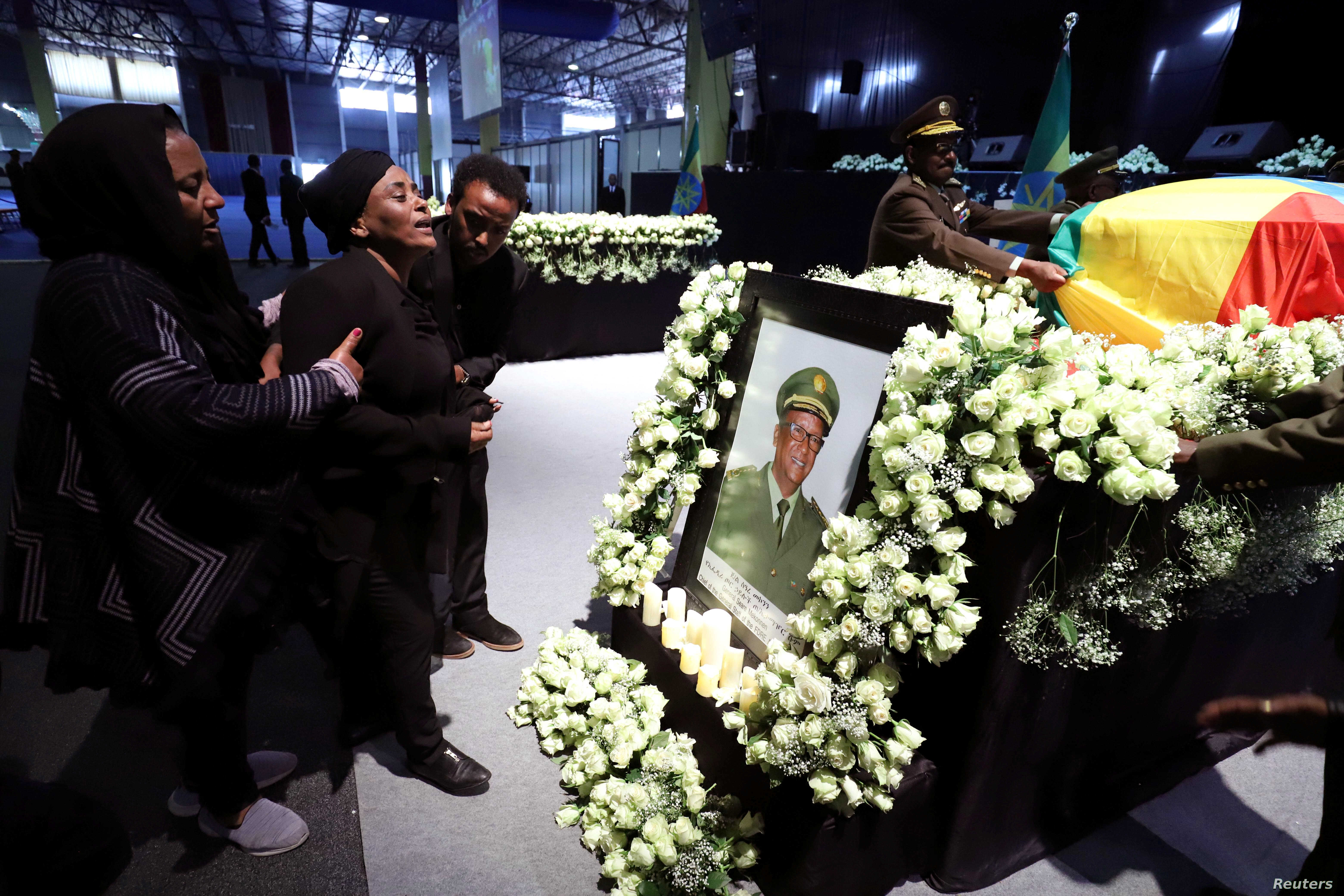 Relatives mourn in front of the coffin of the country's Army Chief of Staff Seare Mekonnen, who was shot by his bodyguard, during a memorial ceremony in Addis Ababa, June 25, 2019.