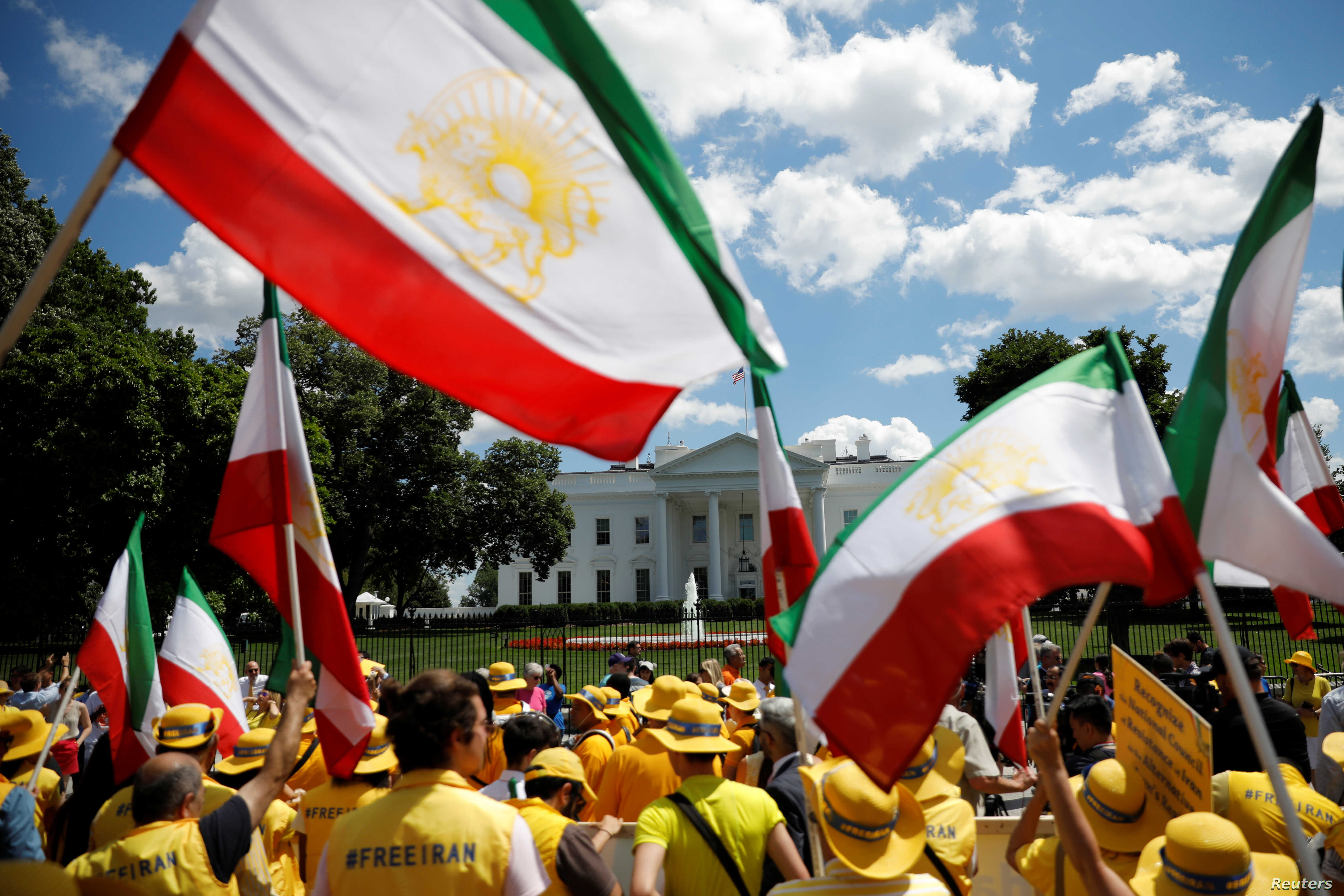 "Activists carry Iranian flags as they hold an ""Uprising for Regime Change"" rally and ""solidarity march with the Iranian resistance"" outside the White House in Washington,  June 21, 2019."