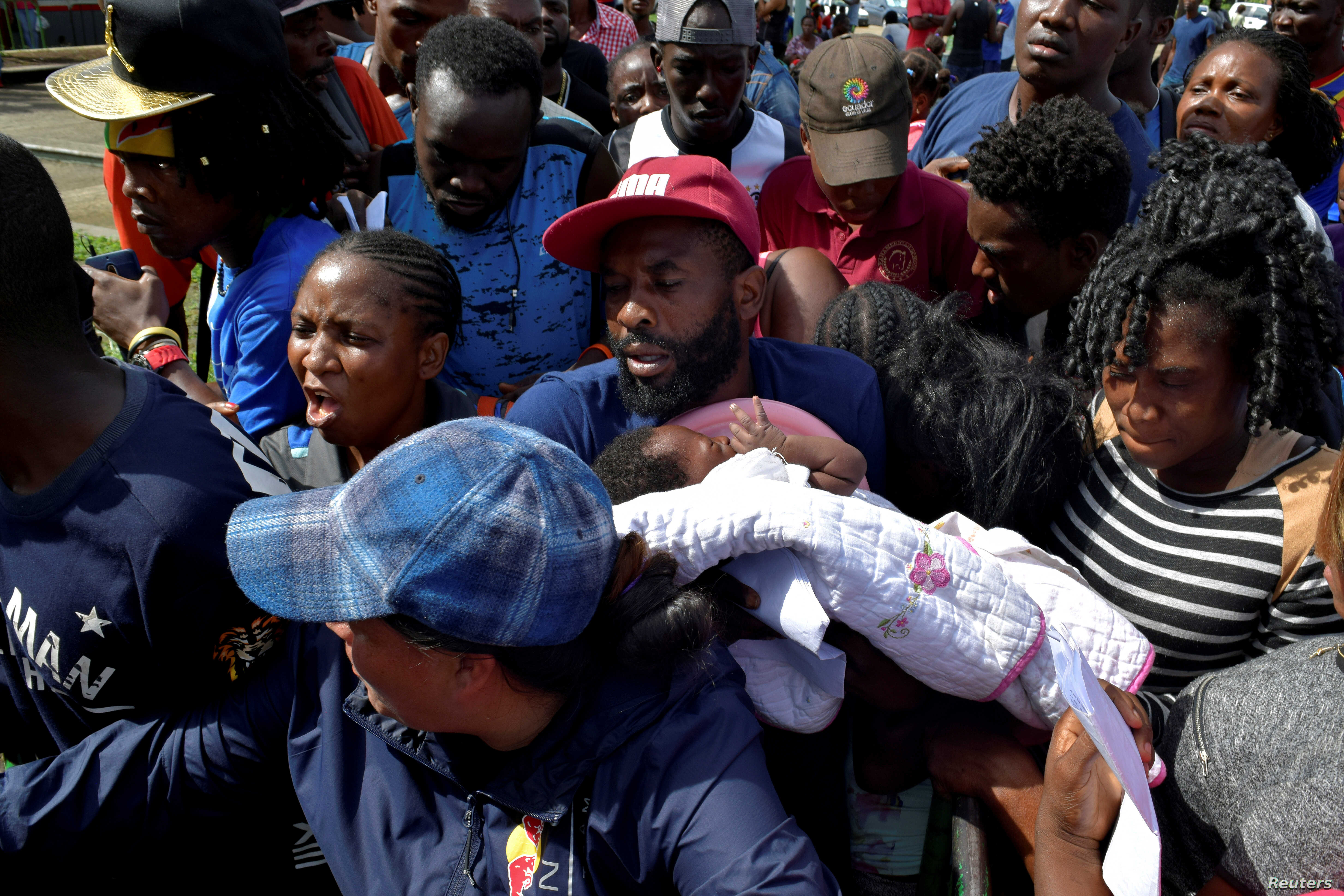 FILE PHOTO: A migrant from Cameroon holds his baby while trying to enter the Siglo XXI immigrant detention center to request humanitarian visas, issued by the Mexican government, to cross the country towards the U.S., in Tapachula, Mexico, July 5, 2019