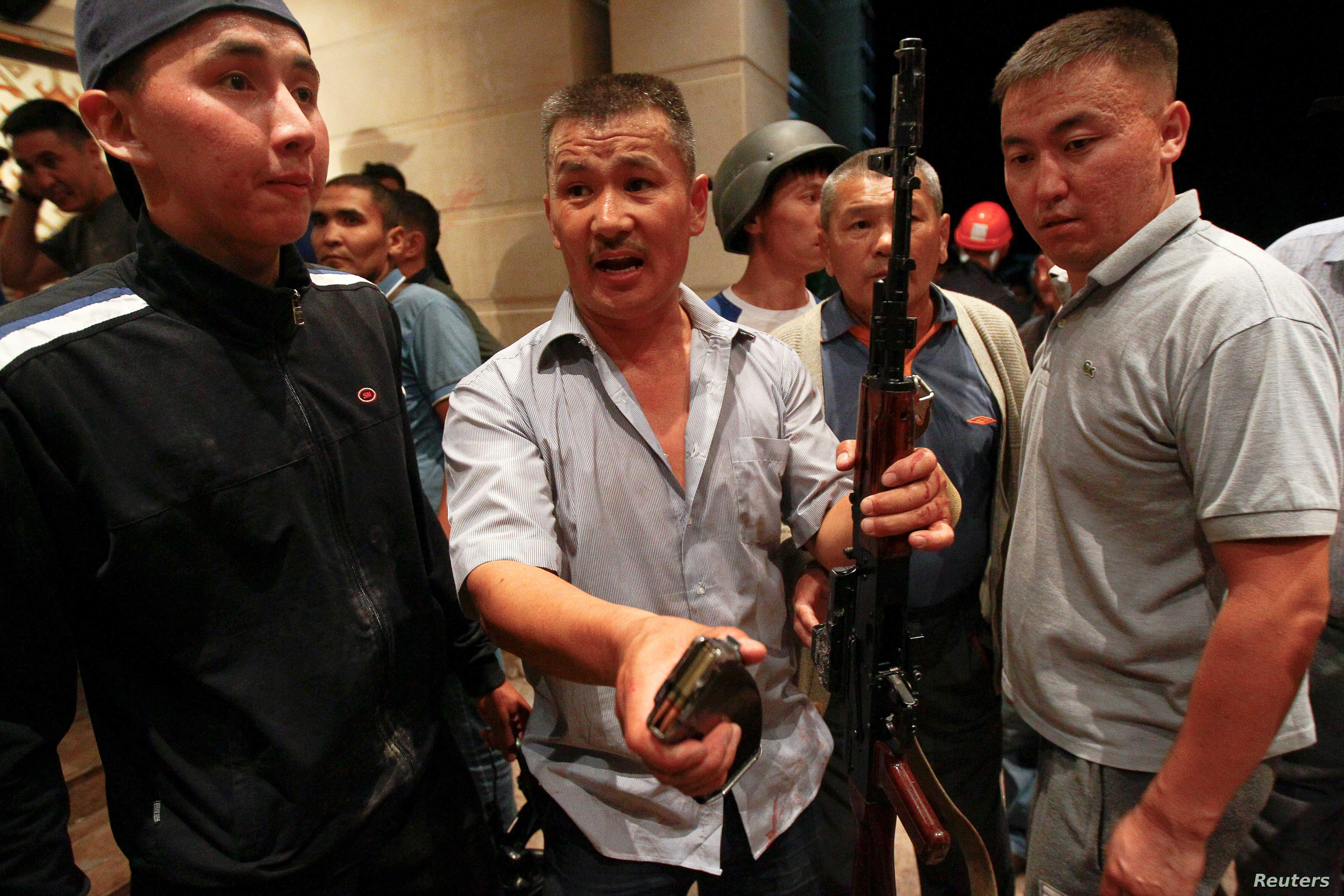 Armed supporters of Kyrgyz former President Almazbek Atambayev guard his house during an operation of state security forces to detain Atambayev, in the village of Koi Tash near Bishkek, Kyrgyzstan, Aug. 7, 2019.