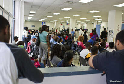 People fill the waiting area of a Pennsylvania Department of Transportation office in Philadelphia as they wait to get a voter ID card, September 27, 2012. Younger Americans, people without college educations, the poor and Hispanics are among the gro...