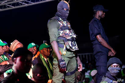 "FILE - Security agents stand guard during the campaign meeting of Issa Sall, presidential candidate and deputy president of the Senegalese ""Parti de l'Unite et du Rassemblement"" (PUR), at the municipal stadium of Thiaroye, a suburb of Dakar, Feb. 3, ..."