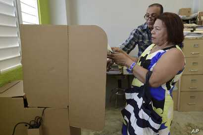 A Puerto Rican resident votes during the fifth referendum on the island's status, in San Juan, Puerto Rico, June 11, 2017.