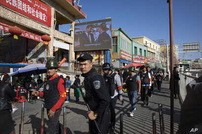 FILE  Armed civilians patrol the area outside the Hotan Bazaar where a screen shows Chinese President Xi Jinping, in Hotan in western China's Xinjiang region, Nov. 3, 2017. Authorities are using detentions in political indoctrination centers and data...