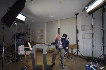 FILE - Dozhd Channel anchor Pavel Lobkov, prepares for a broadcast in their studio-apartment in Moscow, Russia, Dec. 10, 2014.