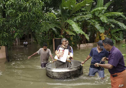 An elderly woman is rescued in a cooking pot after her home was flooded in Thrissur, Kerala state, India, Aug.16, 2018. Torrential monsoon rains have disrupted air and train services in the southern Indian state of Kerala, where flooding, landslides ...