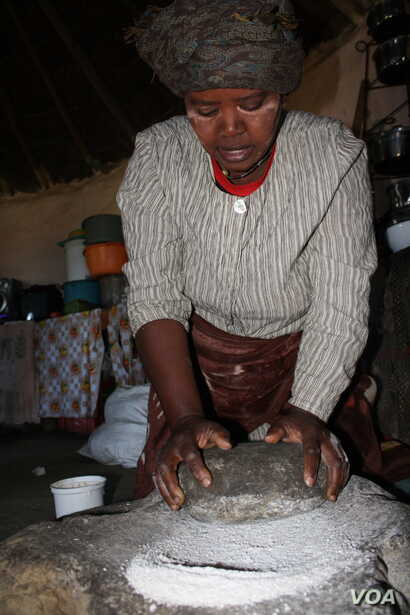 A woman grinds corn to make traditional beer in South Africa's Eastern Cape Province. (D. Taylor/VOA)