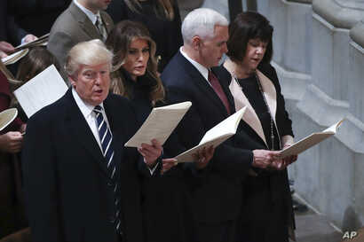 From left, President Donald Trump, first lady Melania Trump, Vice President Mike Pence and his wife Karen, sing together during a National Prayer Service at the National Cathedral, in Washington, Jan. 21, 2017.