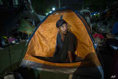 "Joel Eduardo Espinar looks out from his family's tent in the main square of Arriaga, Mexico, Oct. 26, 2018. His plan is to request asylum rather than cross the border illegally. ""I'm kind of fearful of what will happen once we get to the U.S. bor..."