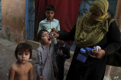 FILE - A Pakistani health worker gives a polio vaccine to a child in Karachi, Pakistan, Dec. 1, 2016. Polio remains endemic in Pakistan after the Taliban banned vaccinations, instigated attacks targeting medical staffers and spread suspicions about t...