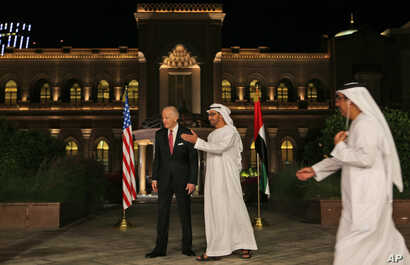 Sheikh Mohammed bin Zayed Al Nahyan, Crown Prince of Abu Dhabi and Deputy Supreme Commander of the UAE Armed Forces, middle, leads Joe Biden, the U.S. Vice President away from the official stage for media coverage at the Emirates Palace in Abu Dhabi,...