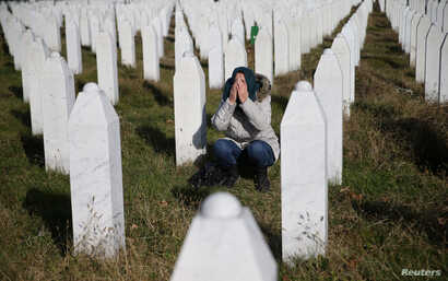 A woman reacts near a grave of her family members in the Memorial centre Potocari near Srebrenica, Bosnia and Herzegovina, after the court proceedings of former Bosnian Serb general Ratko Mladic, Nov. 22, 2017.