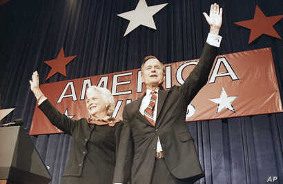 President-elect George H.W. Bush, right, and his wife Barbara Bush, wave to the crowd at a victory celebration rally, Nov. 8, 1988, Houston, Texas.