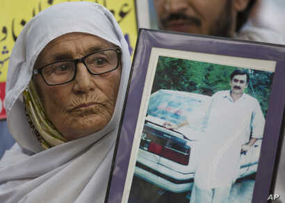 A Pakistani mother holds a picture of her missing son during a rally to observe the International Day of the Disappeared near a Parliament in Islamabad, Pakistan, Aug. 30, 2018.