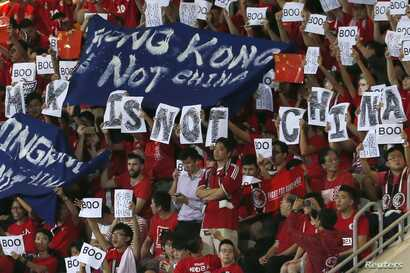 """Hong Kong fans hold banners and character signs that read """"Hong Kong is not China,"""" during the Chinese national anthem at the 2018 World Cup qualifying match between Hong Kong and China, in Hong Kong, Nov. 17, 2015."""