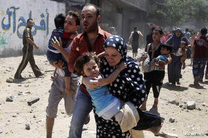 Palestinians run following what police said was an Israeli air strike on a house in Gaza city July 9, 2014. At least 23 people were killed across Gaza, Palestinian officials said.