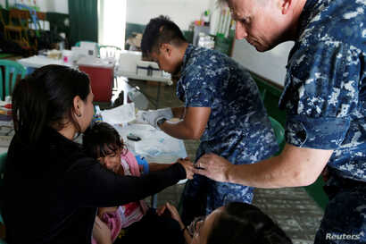 Kamila, daughter of Yenymar Vilches, a Venezuelan migrant, is attended by personnel of the ship of the United States Navy Hospital USNS Comfort at Divina Pastora High School in Riohacha, Colombia Nov. 26, 2018.