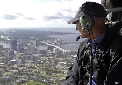 FILE - In this Sept. 12, 2017 photo, Gov. Rick Scott assesses flooding damage over Jacksonville, Fla., in the aftermath of Hurricane Irma.