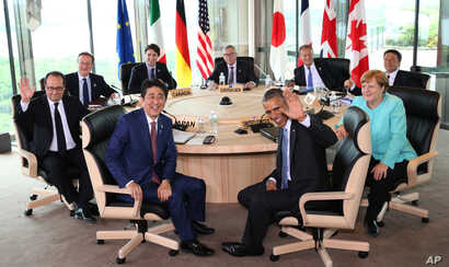 Japanese Prime Minsiter Shinzo Abe, foreground center left, and U.S. President Barack Obama, foreground center right, smile at photographers with other leaders of Group of Seven industrial nations, clockwise from left, French President Francois Holla...