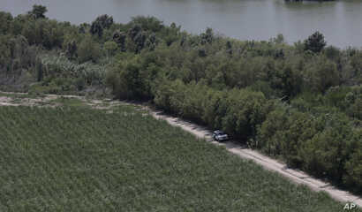 FILE - In this July 24, 2014, photo, a Customs and Border Protection vehicle patrols on the Texas border near the Rio Grande in Mission, Texas.