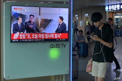 A youth walks past a television screen showing a file image of North Korean leader Kim Jong Un as news anchors provide coverage of a North Korean missile launch, at a railway station in Seoul, Aug. 26, 2017.