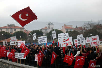 Supporters of President Tayyip Erdogan wave Turkish flags during the first hearing of the trial for soldiers accused of attempting to assassinate Erdogan during last year's failed July 15 coup, in Mugla, Turkey, Feb. 20, 2017.