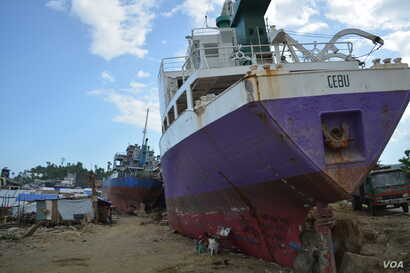 Beached ships among shanties along this seaside community of Anibong.  The city says shipping companies have been given months to remove the ships, if not the government will move them, Tacloban City, Philippines, March 9, 2014. (Simone Orendain/VOA)...