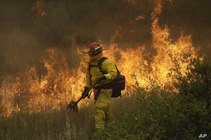 A firefighter with Cal Fire Mendocino Unit walks along a containment line as a wildfire advances, July 30, 2018, in Lakeport, California.